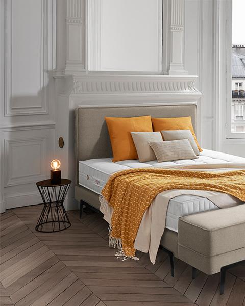 Bett von Treca mit orangen Accessoires